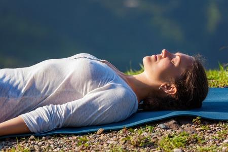 Woman relaxes in yoga relaxation asana Savasana - corpse pose outdoors in Himalayas. Himachal Pradesh, India