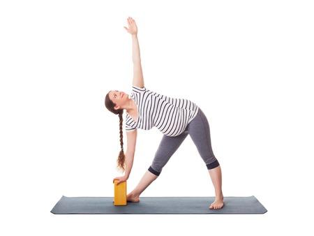 Schwangerschaft Yoga-Übung - schwangere Frau tun Asana Utthita trikonasana - erweiterte Dreieck Pose mit Block auf weißem Hintergrund Standard-Bild - 60025703