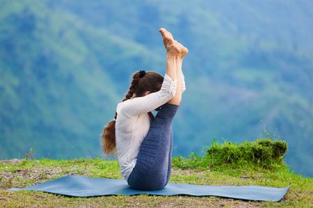 ashtanga: Yoga - sporty fit woman practices Ashtanga Vinyasa yoga asana Urdhva mukha paschimottanasana - upward facing intense west stretch oudoors