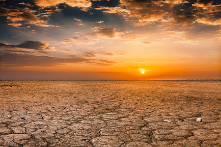 scorched: Global worming concept - cracked scorched earth soil drought desert landscape dramatic sunset Stock Photo