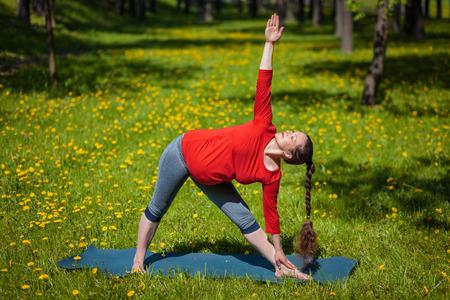 trikonasana: Pregnancy yoga exercise - pregnant woman doing asana Utthita trikonasana outdoors on grass in summer