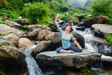 pada: Hatha yoga outdoors - young sporty fit woman doing yoga asana Eka pada rajakapotasana - one-legged king pigeon pose at tropical waterfall. Himachal Pradesh, India