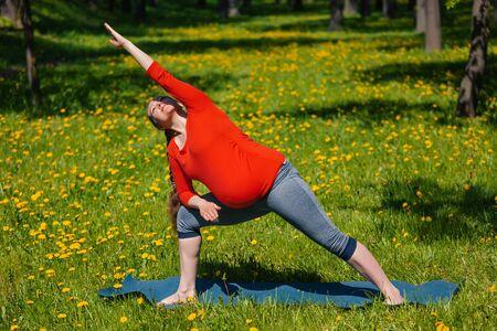 yogic: Pregnancy yoga exercise - pregnant woman doing asana Utthita parsvakonasana outdoors on grass in summer Stock Photo