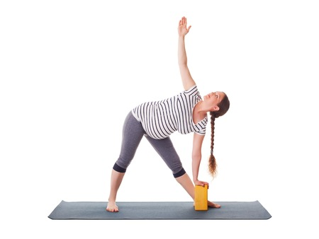 trikonasana: Pregnancy yoga exercise - pregnant woman doing asana Utthita trikonasana - extended triangle pose with block isolated on white background