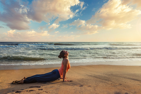 Yoga outdoors on beach - woman practices Ashtanga Vinyasa yoga Surya Namaskar Sun Salutation asana Urdhva Mukha Svanasana - upward facing dog pose on sunset. Kerala, India Stock Photo