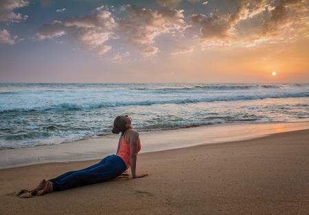 ashtanga: Yoga outdoors on beach - woman practices Ashtanga Vinyasa yoga Surya Namaskar Sun Salutation asana Urdhva Mukha Svanasana - upward facing dog pose on sunset. Kerala, India Stock Photo