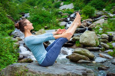 ashtanga: Yoga outdoors - young sporty fit woman doing Ashtanga Vinyasa Yoga asana Navasana - boat pose  - in Himalayas at tropical waterfall. Himachal Pradesh, India