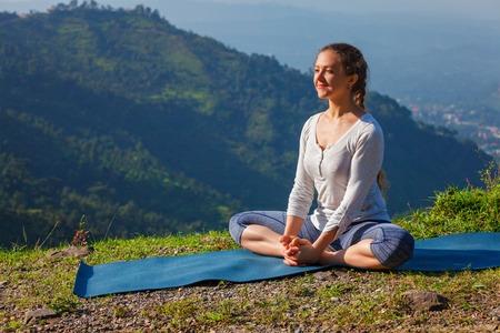 baddha: Sporty fit woman practices yoga asana Baddha Konasana - bound angle pose outdoors in HImalayas mountains in the morning with sky. Himachal Pradesh, India