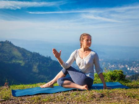 ardha: Yoga exercise outdoors -  woman doing Ardha matsyendrasanaasana asana - half spinal twist pose mountains in Himalayas in India in the morning