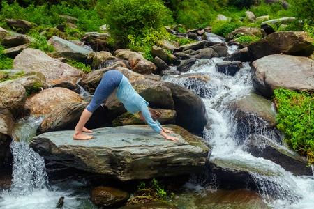 namaskar: Young sporty fit woman doing yoga asana Adho mukha svanasana - downward facing dog - of Surya Namaskar Sun Salutation at tropical waterfall