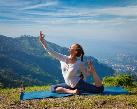 pada: Yoga outdoors - young sporty fit woman doing stretching yoga asana Eka pada rajakapotasana - one-legged king pigeon pose in Himalayas mountains, India Stock Photo