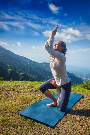 ashtanga: Young woman doing Ashtanga Vinyasa yoga advanced difficult asana Vatayanasana (Horse pose) outdoors in Himalayas mountains. Himachal Pradesh, India Stock Photo