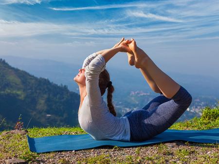 Yoga outdoors - young sporty fit woman doing Ashtanga Vinyasa Yoga asana Dhanurasana - bow pose - in Himalayas mountains in the morning Himachal Pradesh, India Stock Photo