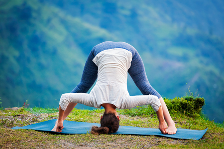 to bend: Yoga exercise outdoors -  woman doing Ashtanga Vinyasa Yoga asana Prasarita padottanasana  D - wide legged forward bend pose outdoors