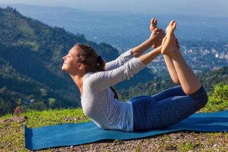 ashtanga: Yoga outdoors - young sporty fit woman doing Ashtanga Vinyasa Yoga asana Dhanurasana - bow pose - in Himalayas mountains in the morning Himachal Pradesh, India Stock Photo
