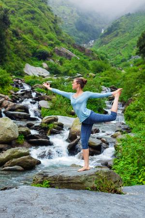 nataraja: Yoga outdoors - woman doing yoga asana Natarajasana - Lord of the dance balance pose outdoors at waterfall in Himalayas