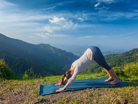 namaskar: Yoga outdoors. Young sporty fit woman doing Ashtanga Vinyasa Yoga asana Adho mukha svanasana - downward facing dog - in Surya Namaskar Sun Salutation outdoors in Himalayas in the morning Stock Photo