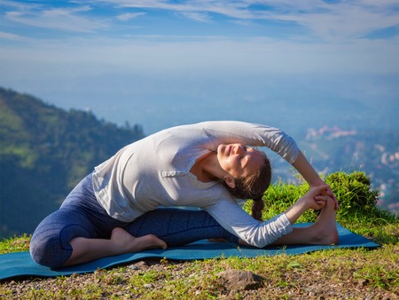 hatha: Yoga outdoors - young sporty fit woman doing Hatha Yoga asana parivritta janu sirsasana - Revolved Head-to-Knee Pose - in mountains in the morning