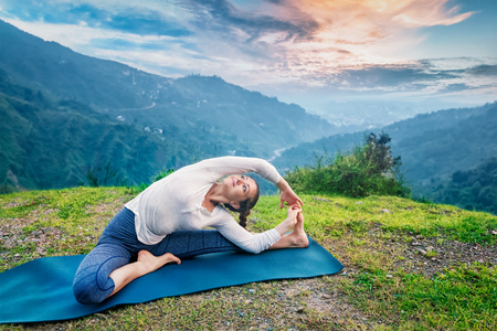 revolved: Yoga outdoors - young sporty fit woman doing Hatha Yoga asana parivritta janu sirsasana - Revolved Head-to-Knee Pose - in