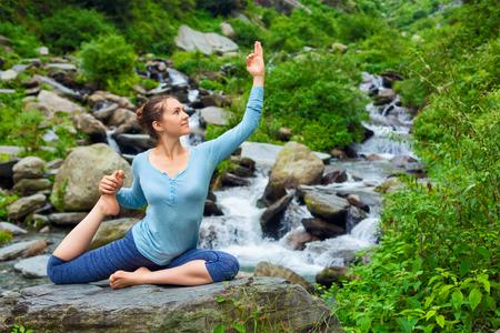 hatha: Hatha yoga outdoors - young sporty fit woman doing yoga asana Eka pada rajakapotasana - one-legged king pigeon pose at tropical waterfall. Himachal Pradesh, India