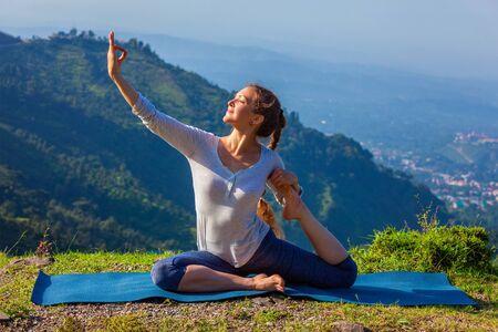 eka: Yoga outdoors - young sporty fit woman doing stretching yoga asana Eka pada rajakapotasana - one-legged king pigeon pose in Himalayas mountains, India Stock Photo