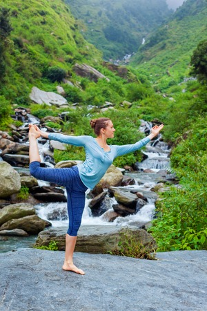 Yoga outdoors - woman doing yoga asana Natarajasana - Lord of the dance balance pose outdoors at waterfall in Himalayas