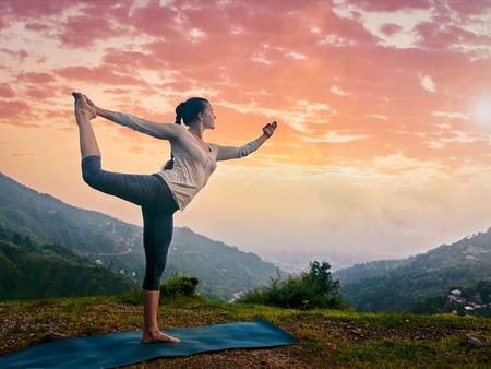 nataraja: Woman doing yoga asana Natarajasana - Lord of the dance pose outdoors at waterfall in Himalayas