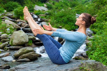 ashtanga: Yoga outdoors - young sporty fit woman doing Ashtanga Vinyasa Yoga asana Navasana - boat pose - in Himalayas at tropical waterfall. Himachal Pradesh, India Stock Photo