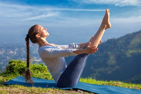 ashtanga: Yoga outdoors - young sporty fit woman doing Ashtanga Vinyasa Yoga asana Navasana - boat pose  - in Himalayas mountains in the morning  Himachal Pradesh, India