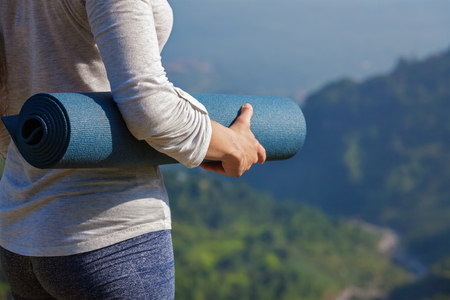 Woman standing with yoga mat outdoors in mountains close up with copyspace getting ready for yoga exercise