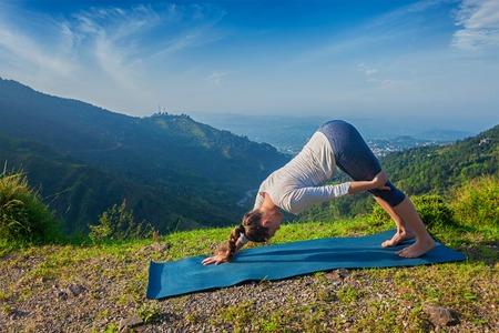 ashtanga: Yoga outdoors - young sporty fit woman doing Ashtanga Vinyasa Yoga asana Adho mukha svanasana - downward facing dog variation - outdoors in Himalayas in the morning