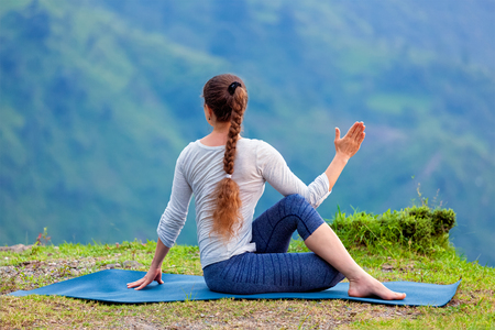 Hatha yoga outdoors - sporty fit woman doing yoga asana Parivrtta Marichyasana (or ardha matsyendrasana) -  seated spinal twist outdoors in mountains
