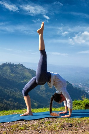 eka: Yoga outdooors - woman doing yoga asana eka pada urdva dhanurasana Upward Bow Pose back bend outdoors in Himalayas in the morning