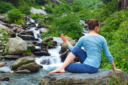 yogic: Yoga exercise outdoors -  woman doing Ardha matsyendrasanaasana asana - half spinal twist pose at tropical waterfall in Himalayas in India