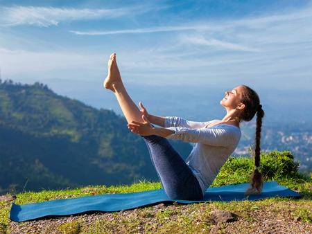 ashtanga: Yoga outdoors - young sporty fit woman doing Ashtanga Vinyasa Yoga asana Navasana - boat pose - in Himalayas mountains in the morning Himachal Pradesh, India Stock Photo