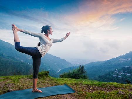 woman healthy: Woman doing yoga asana Natarajasana - Lord of the dance pose outdoors at waterfall in Himalayas