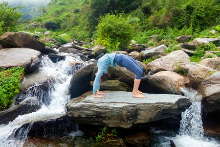 dhanurasana: Yoga outdoors - young sporty fit woman doing Ashtanga Vinyasa Yoga asana Urdhva Dhanurasana - upward bow pose at tropical waterfall