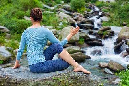 ardha: Yoga exercise outdoors - woman doing Ardha matsyendrasanaasana asana - half spinal twist pose at tropical waterfall in Himalayas in India