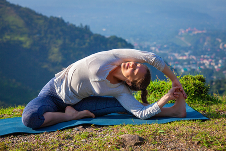 Yoga outdoors - young sporty fit woman doing Hatha Yoga asana parivrtta janu sirsasana - Revolved Head-to-Knee Pose - in mountains in the morning