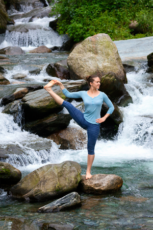 hasta: Yoga outdoors - woman doing Ashtanga Vinyasa Yoga balance asana Utthita Hasta Padangushthasana - Extended Hand-To-Big-Toe Pose position posture outdoors at waterfall Stock Photo