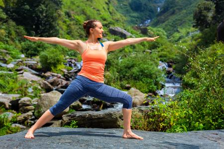 ashtanga: Yoga outdoors - sporty fit woman doing Ashtanga Vinyasa Yoga asana Virabhadrasana 2 Warrior pose posture at tropical waterfall