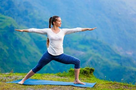 yogic: Yoga outdoors - sporty fit woman doing Ashtanga Vinyasa Yoga asana Virabhadrasana 2 Warrior pose posture in mountains