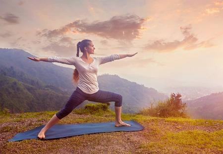 warrior pose: Yoga outdoors - sporty fit woman doing Ashtanga Vinyasa Yoga asana Virabhadrasana 2 Warrior pose posture in mountains