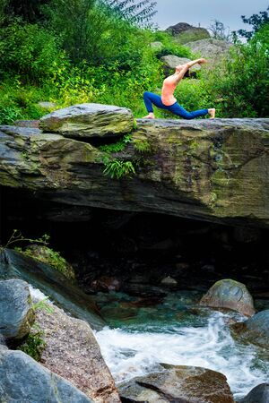 yogic: Yoga outdoors - sporty fit woman practices yoga Anjaneyasana - low crescent lunge pose outdoors in mountains