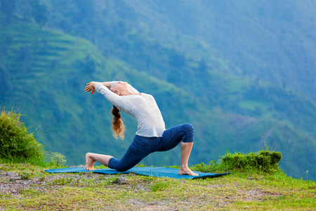 hatha: Yoga outdoors - sporty fit woman practices Hatha yoga asana Anjaneyasana - low crescent lunge pose posture outdoors in Himalayas mountains