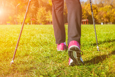 walking pole: Nordic walking adventure and exercising concept - woman hiking, legs and nordic walking poles in summer nature. With lens flare and light leak. Stock Photo