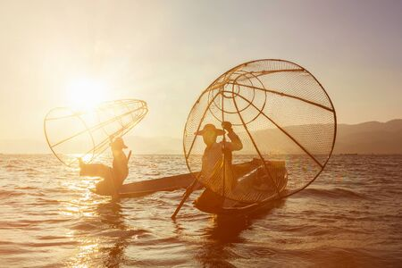 sunrises: Myanmar travel attraction landmark - two traditional Burmese fishermen at Inle lake, Myanmar famous for their distinctive one legged rowing style on sunrise sunset