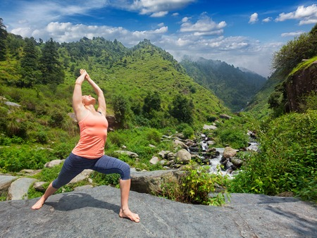 ashtanga: Yoga outdoors - sporty fit woman doing Ashtanga Vinyasa Yoga asana Virabhadrasana 1 Warrior pose posture at waterfall in HImalayas mountains