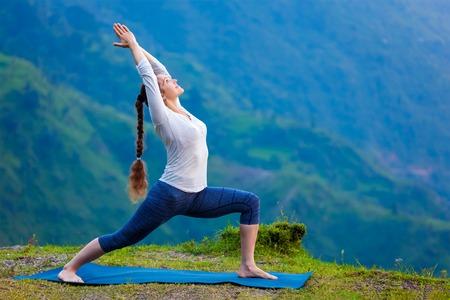warrior pose: Yoga outdoors - sporty fit woman doing Ashtanga Vinyasa Yoga asana Virabhadrasana 1 Warrior pose posture in HImalayas mountains