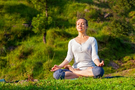 baddha: Young sporty fit woman doing yoga outdoors - meditating and relaxing in Padmasana Lotus Pose) with chin mudra on green grass in forest Stock Photo
